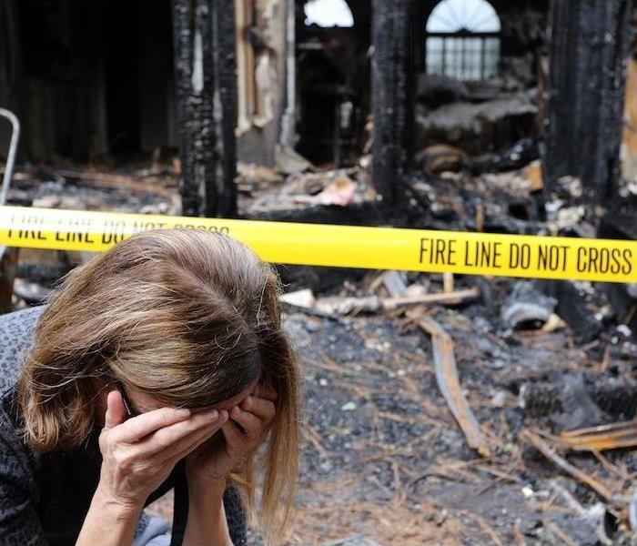 woman with hands covering face upset with burnt house in